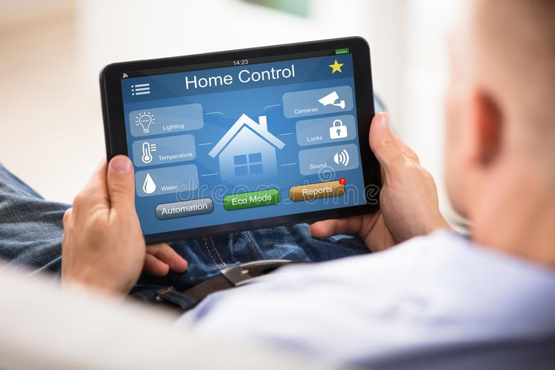 Man Using Home Control System On Digital Tablet royalty free stock photos