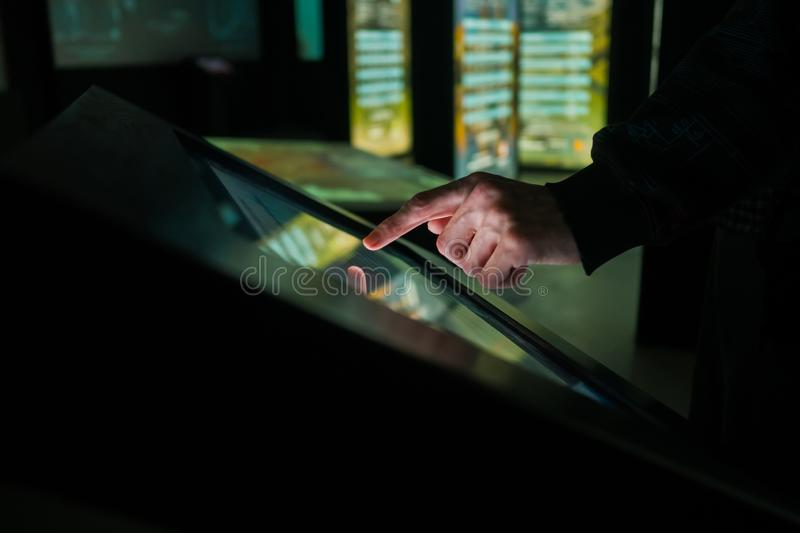 Man using interactive touchscreen display at modern museum or exhibition. Man using interactive touchscreen display of electronic multimedia kiosk at modern royalty free stock image