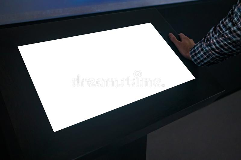Man using interactive white empty touchscreen display kiosk at exhibition. Man looking at white blank interactive touchscreen display of electronic multimedia royalty free stock photo