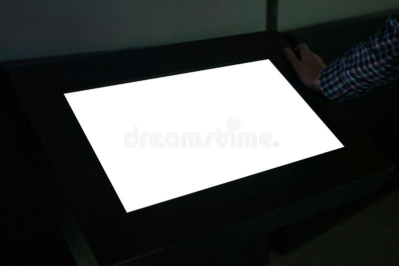 Man using interactive white empty touchscreen display kiosk at exhibition. Man looking at white blank interactive touchscreen display of electronic multimedia stock photography