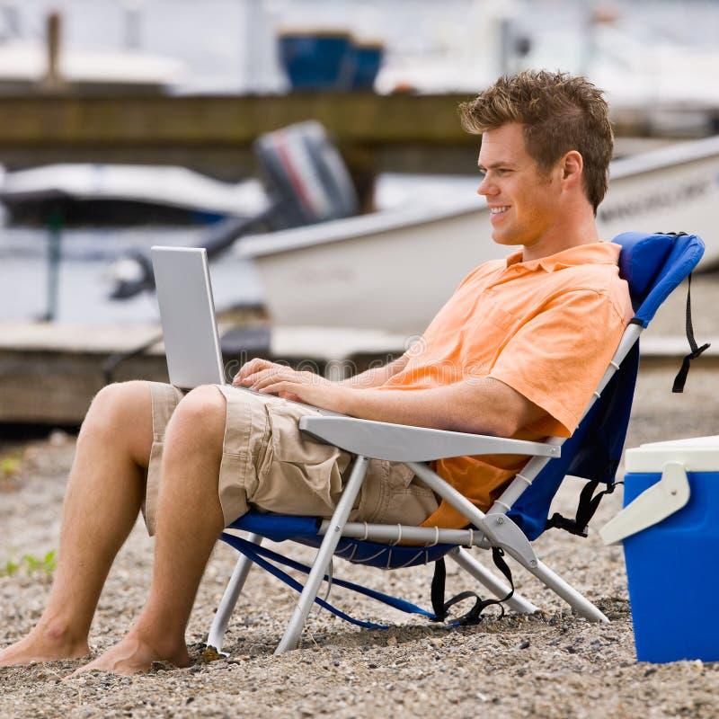 Download Man Using Laptop On Beach Stock Photos - Image: 7379453