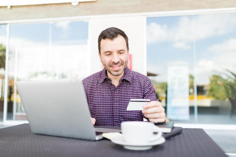Man Using Laptop And Credit Card In Shopping Mall royalty free stock photos