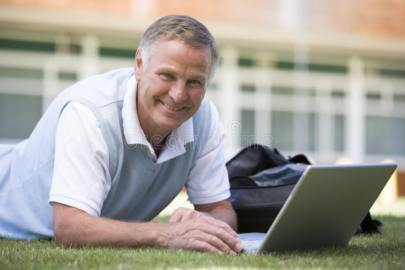 Man using laptop while lying in grass on campus.  royalty free stock photography