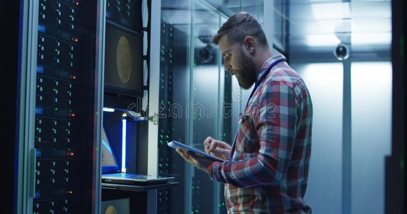 Man using laptop on mining farm in data center royalty free stock images
