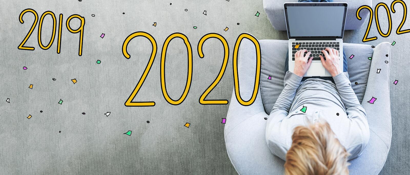 2020 with man using a laptop. In a modern gray chair royalty free stock photos