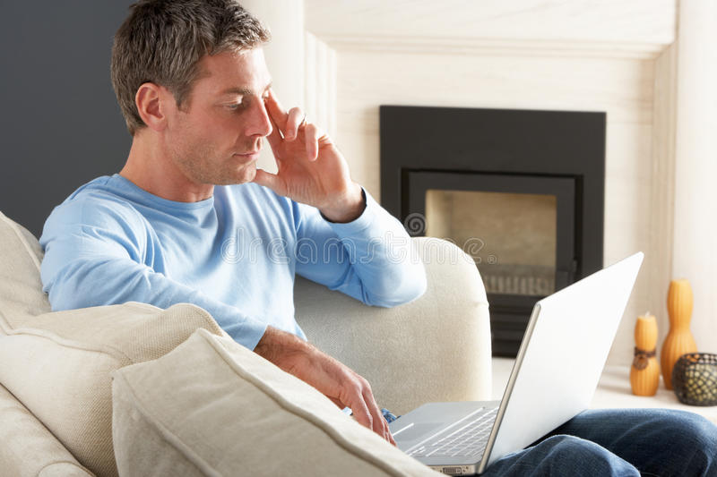 Man Using Laptop Relaxing Sitting On Sofa At Home stock images