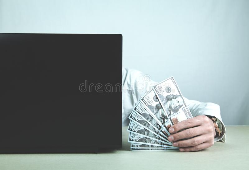 Man using laptop and showing money. Concept of Internet Money stock photo