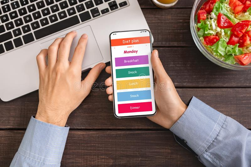 Man using laptop and smartphone with daily diet plan application. Diet plan. Man using laptop and smartphone with daily menu application on screen, vegetable royalty free stock photo
