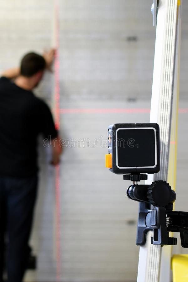 Man using laser level measuring tool in construction work royalty free stock photos