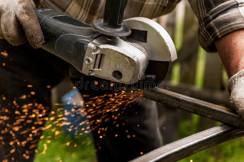 Man using machine for grinding metal at his backyard stock image