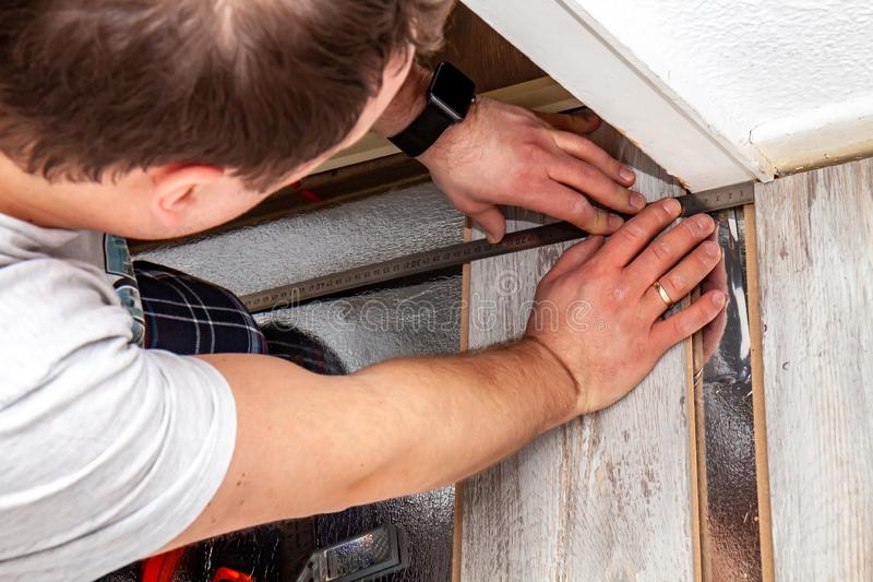 Man using measuring elbow and pencil while installing new wooden laminate flooring at home. stock photo