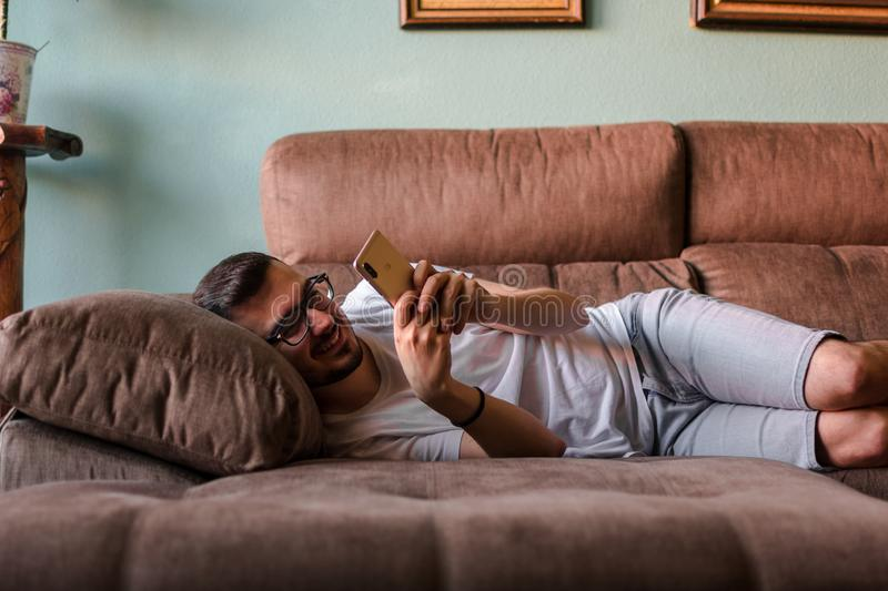 Man using mobile phone while lying on sofa at home royalty free stock photography