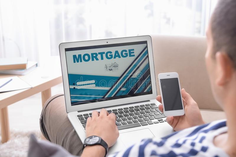 Man using mobile phone while paying mortgage loan online at home royalty free stock images
