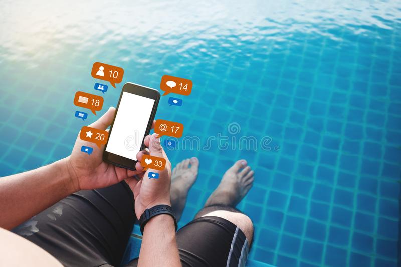 A man using mobile phone at poolside in summer with social media and online message notification icons, blank white screen stock image