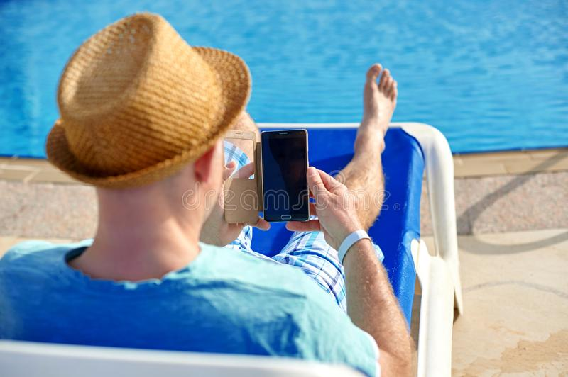 Man using mobile phone on vacation by the pool in hotel, concept of a freelancer working for himself on vacation and stock images