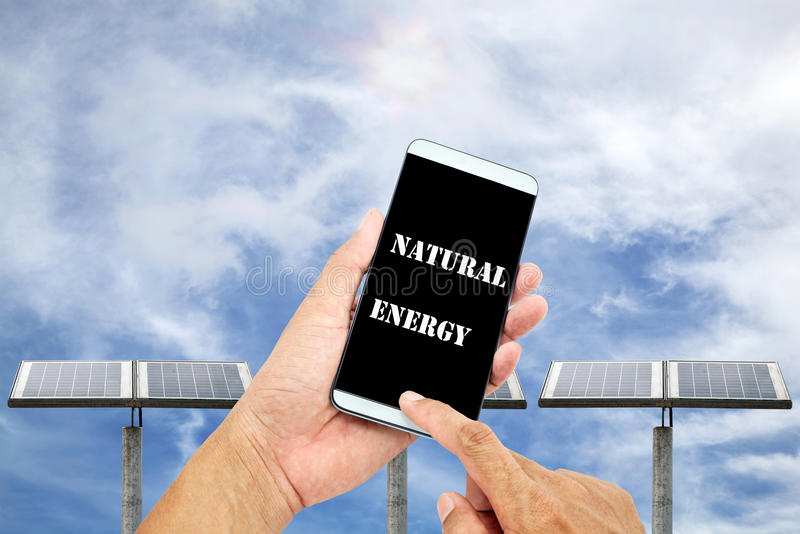 Man using mobile smart phone control with Outdoor small solar pa. Nel on sky background ,natural energy concept stock images