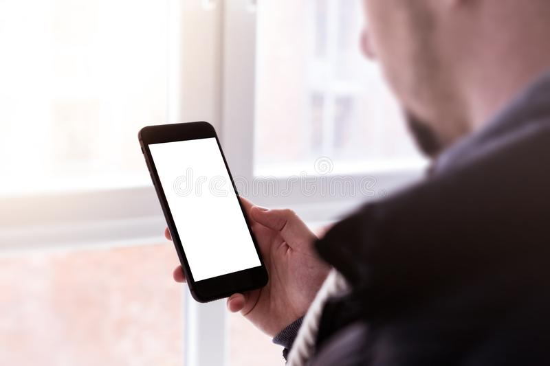 Man using modern mobile smartphone. Shot with third-person view, blank screen. stock photography