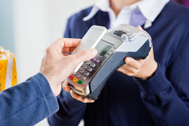 Man Using NFC Technology To Pay Bill At Cinema. Cropped image of men using NFC technology to pay bill at cinema royalty free stock photography