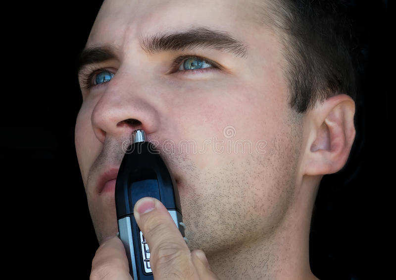 Man using nose hair trimmer. Man removes hair from the nose on an black background royalty free stock photos