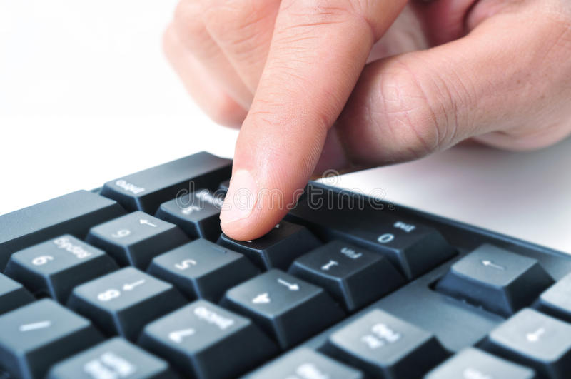 Man using the numeric keypad of a computer keyboard. Closeup of the hand of a man using the numeric keypad of a computer keyboard stock photography