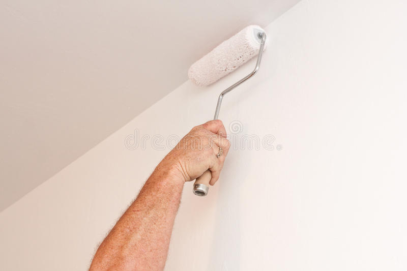 Download Man Using Paint Roller On White Wall Stock Photo - Image: 23779996
