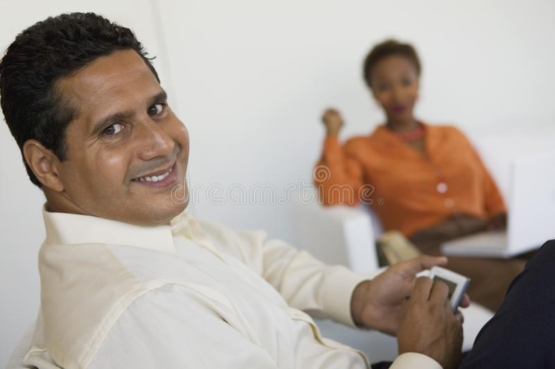 Man using PDA, woman in background stock photos