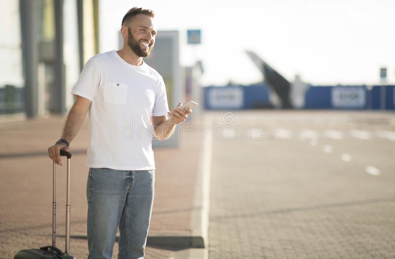 Man using phone app for ordering taxi, arriving at airport. And waiting cab, free space royalty free stock image