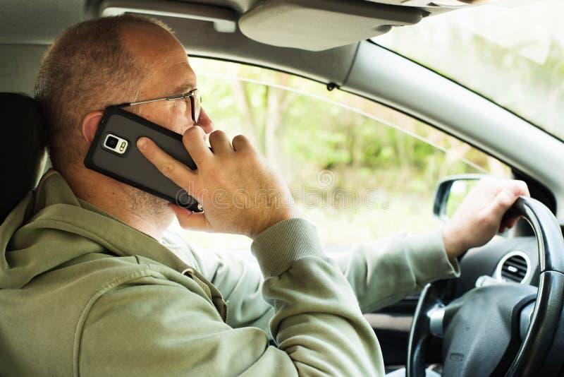Man using phone while driving royalty free stock photos