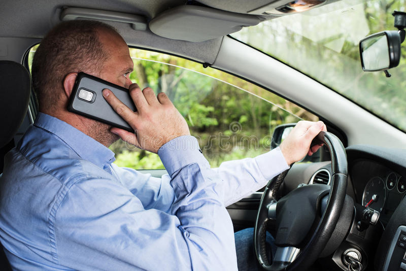 Man using phone while driving stock images