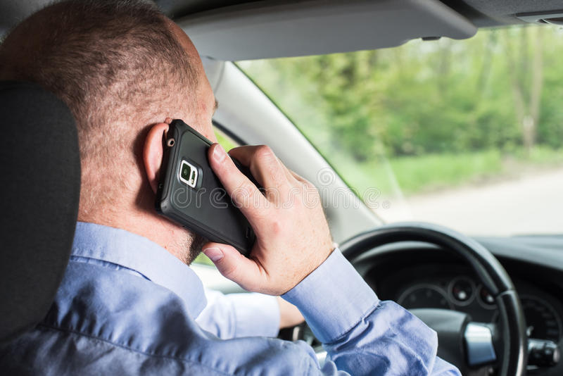 Man using phone while driving royalty free stock photography