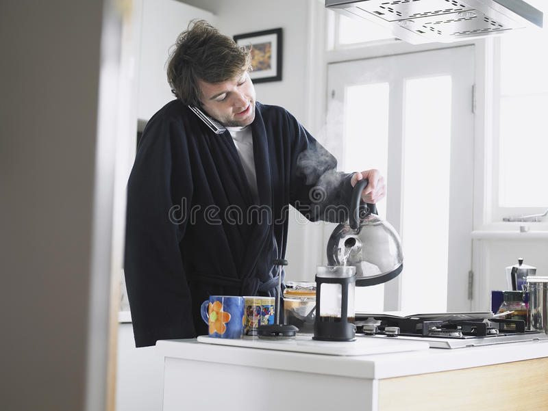 Man Using Phone Pouring Water Into Coffee Plunger. Young man using phone while pouring water into coffee plunger in kitchen royalty free stock photos
