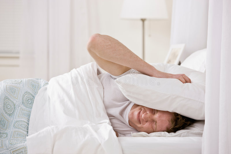 Man using pillow to block out noise. Annoyed man using pillow to block out noise while trying to sleep royalty free stock image