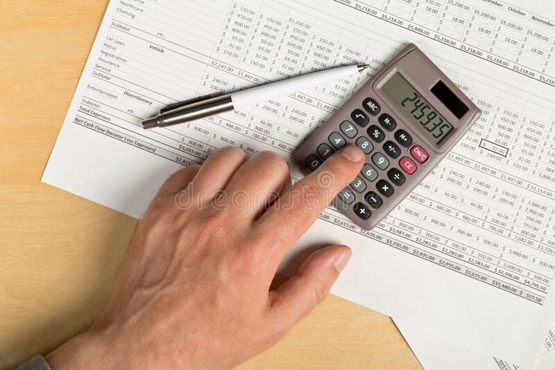 Man using pocket calculator with pen on financial analysis sheet background on wooden office desk - tax, finance or accounting stock photography
