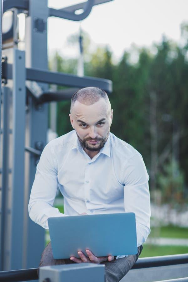 Man using a portable computer. Handsome man using a portable computer on an outdoor stock image