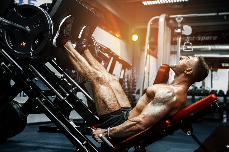 Man Using A Press Machine In A Fitness Club. Strong man doing an exercise on its feet in the simulator. royalty free stock photos