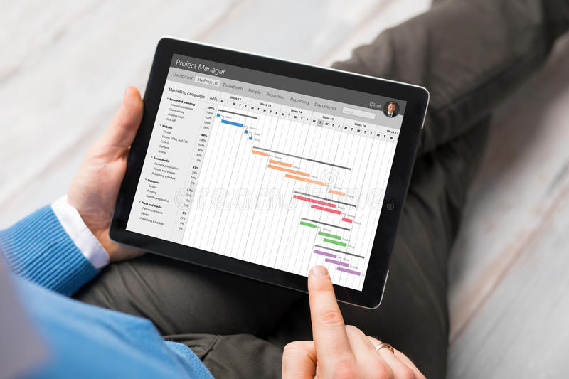 Man using project management app on tablet. Computer stock images