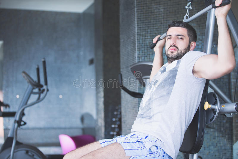Man using pull down machine in gymnasium.Handsome muscular man exercising on pull down machine. royalty free stock image