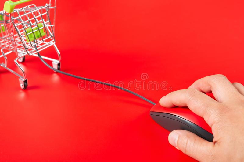 Man using red mouse connected to a shopping cart on red background stock photo