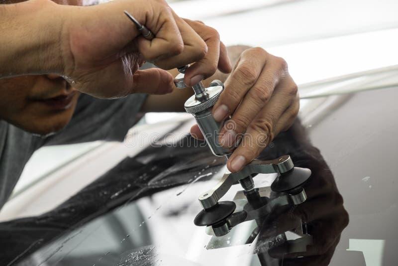 A man using repairing equipment to fix damaged windshield stock photo