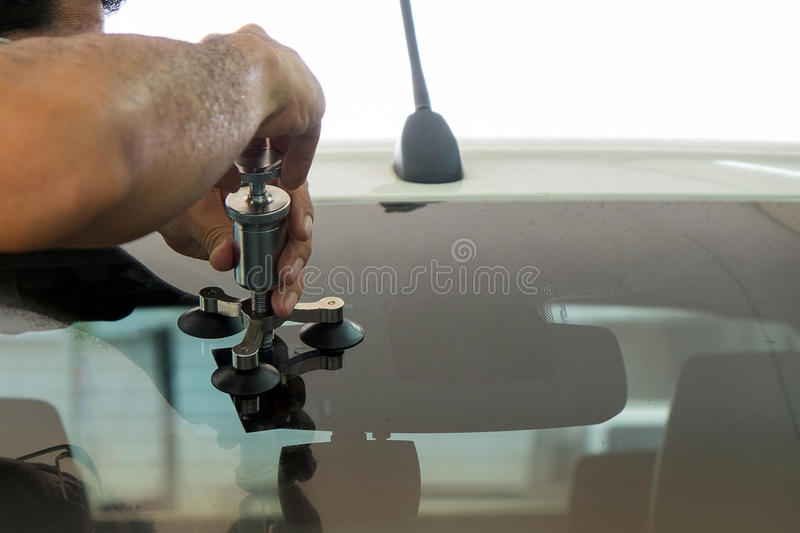 A man using repairing equipment to fix damaged windshield royalty free stock photos