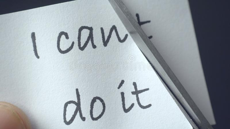 Man using scissors to remove the word can`t to read I can do it stock photography