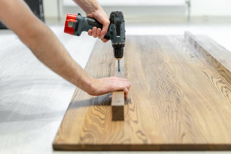 Man using screwdriver fasten plank on wooden table top. Side view and closeup photo of carpenter person using professional electric screwdriver instrument and royalty free stock photos