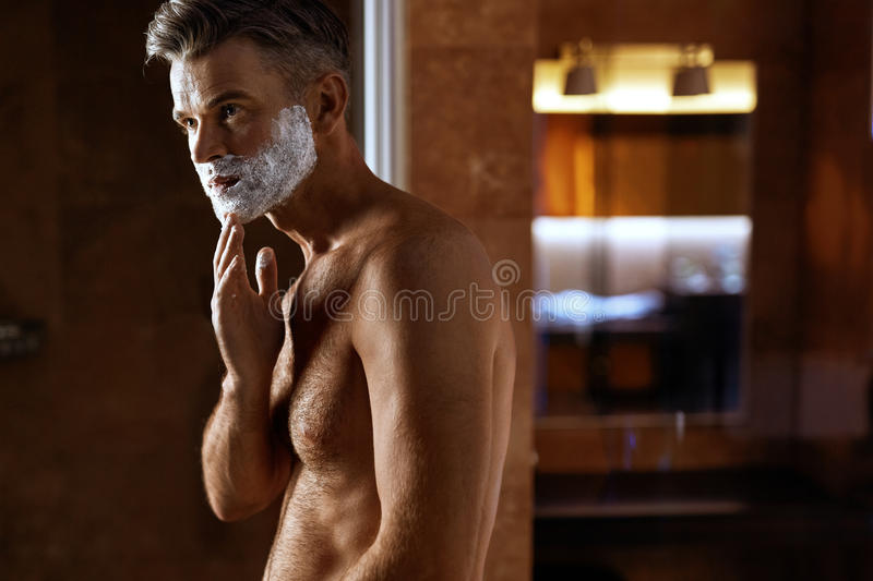 Man Using Shaving Cream On Face In Bathroom. Men Skin Care royalty free stock image