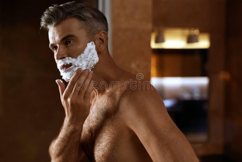 Mature man applying face cream close up high