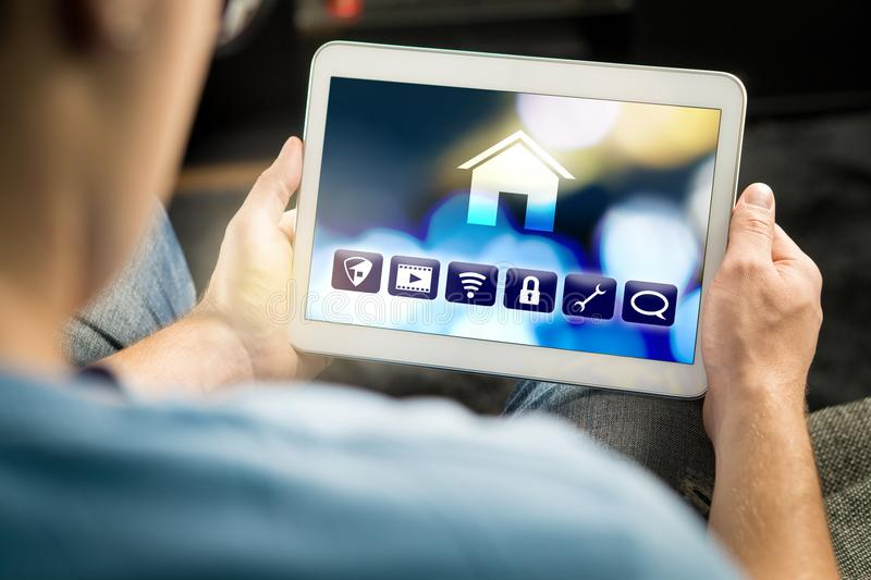 Man using smart home application in tablet to control house royalty free stock photo