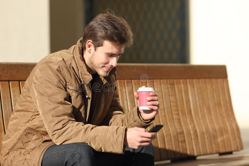 Man using a smart phone and holding a coffee cup. Sitting in a bench in the street stock photography