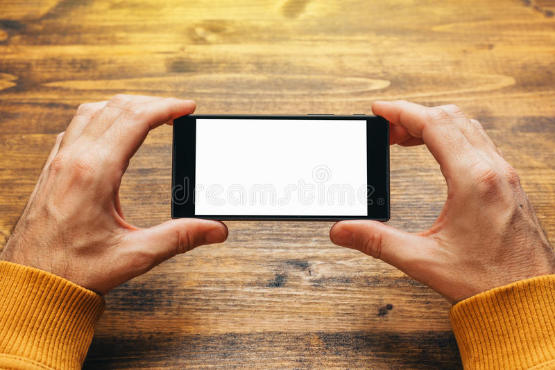 Man using smart phone in horizontal landscape orientation. For streaming movies or browsing picture gallery, blank screen as copy space royalty free stock photo
