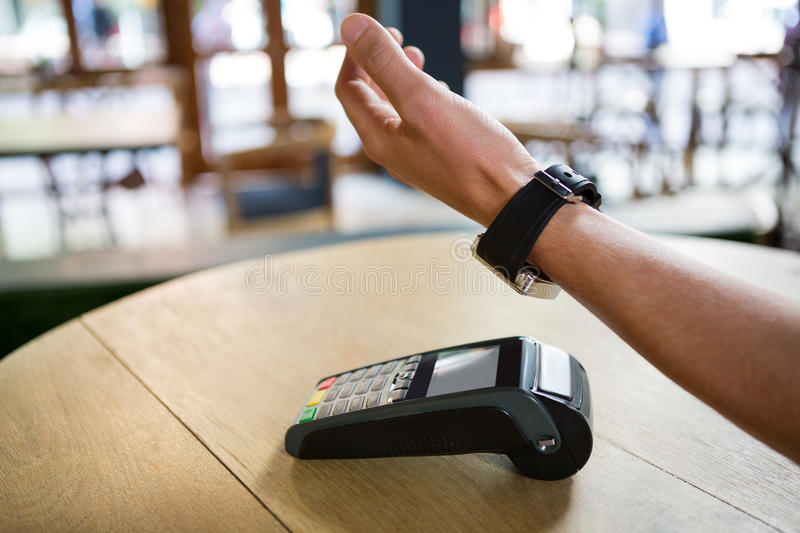 Man using smart watch to express pay in coffee shop royalty free stock photography