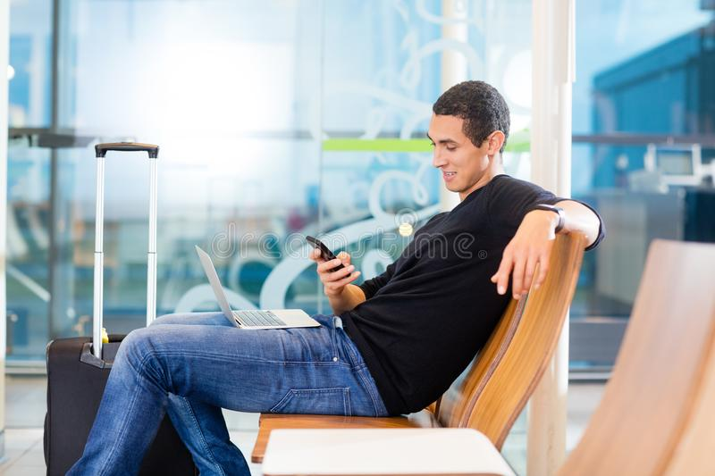 Man Using Smartphone In Airport Waiting Area stock photography