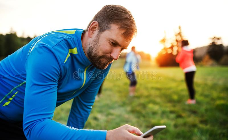 A man using smartphone after doing exercise in nature. stock image
